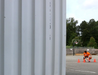 MARIO BARTEL/THE TRI-CITY NEWS Stacks of shipping containers, and crooked fibreboard fencing are the backdrop for makeshift basketball courts constructed in a parking lot behind BC Christian Academy so Panther Hoops could conduct its summer youth camps.